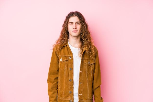 Молодой человек с длинными волосами, позирует, изолированные, счастливые, улыбающиеся и веселые.