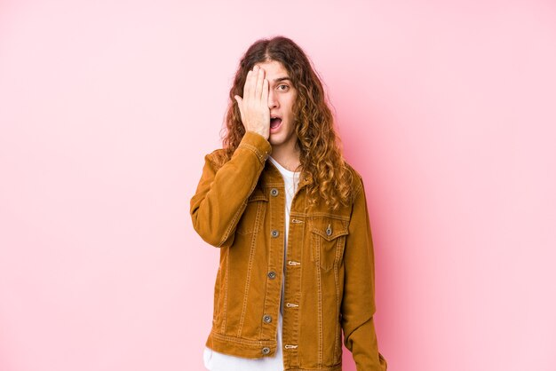 Young long hair man posing isolated having fun coning half of face with palm.