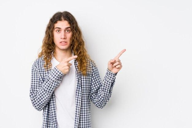 Молодой человек с длинными волосами, позирующий изолированно в шоке, указывая указательными пальцами на копию пространства.