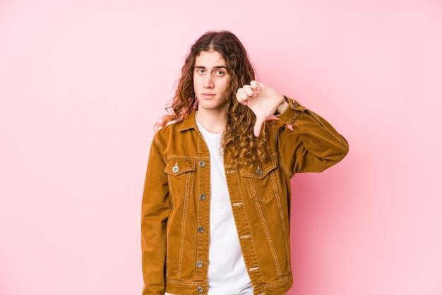 Молодой человек с длинными волосами позирует изолированно, показывая жест неприязни, пальцы вниз