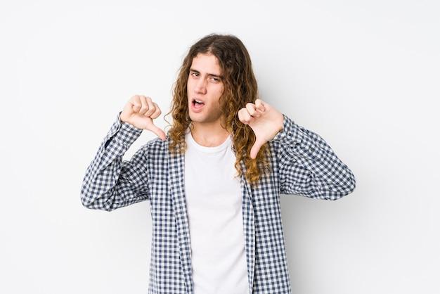 Молодой человек с длинными волосами позирует изолированно, показывая большой палец вниз и выражая неприязнь.