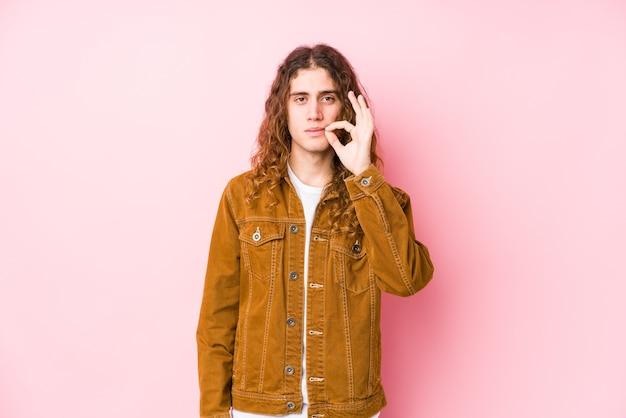 Молодой человек с длинными волосами позирует изолированным с пальцами на губах, хранящих в секрете.