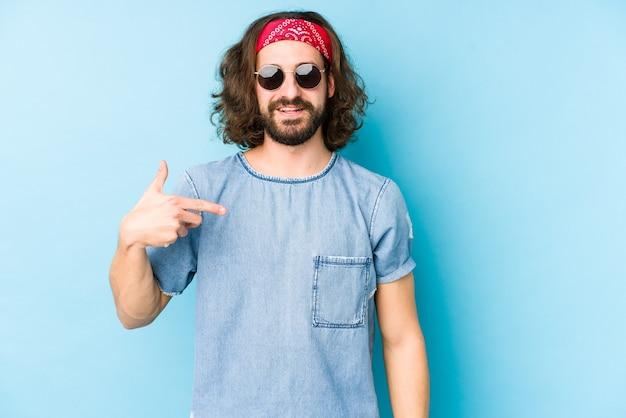 祭りのヒップスターを身に着けている若い長い髪の男は、シャツのコピースペースを手で指している孤立した人に見え、誇りと自信を持っています