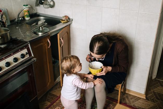 Молодая длинноволосая красивая мать готовит еду на кухне для своей маленькой смешной дочери. крытый милая девушка портрет.