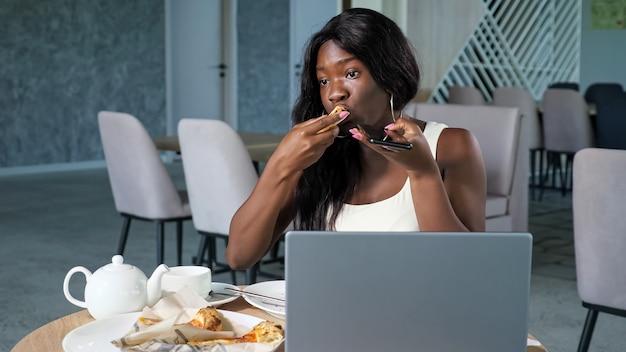 젊은 장발 흑인 여성은 밝은 현대식 카페 테이블에 있는 열린 현대식 노트북 근처에서 확성기 모드를 사용하여 피자 대화를 먹습니다.