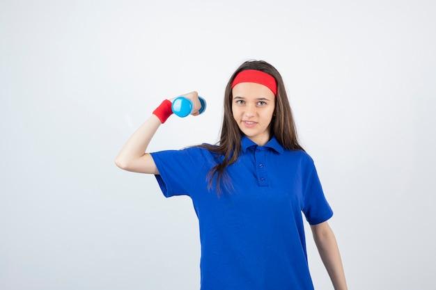 ウェイトダンベルでヘッドバンドトレーニングの若い長い髪の少女。