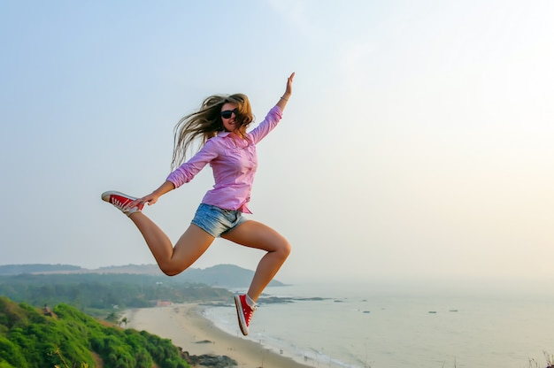 Young long-haired girl in shorts and red sneakers jumps high against stunningly beautiful landscape with the sea and hills. youth, freedom, travel, adventure