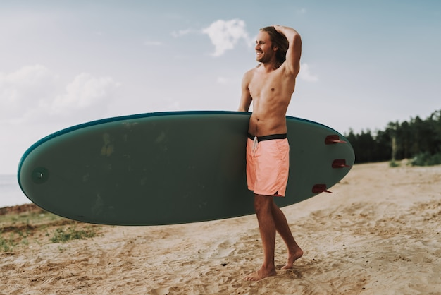 Young long haired guy with surf standing on beach.