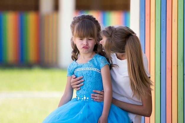 Молодая длинноволосая мать или сестра держатся за колени и обнимают довольно маленькую капризную неудовлетворенную девушку в синем платье