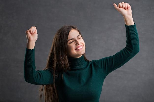 濃い緑色のセーターを着た若い長髪の女性