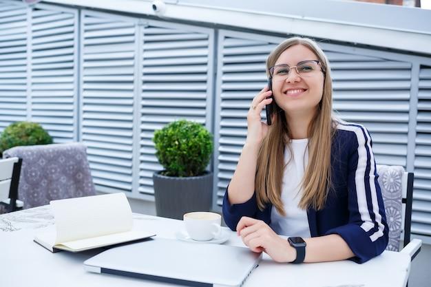 Молодая длинноволосая женщина разговаривает по мобильному телефону, работает с ноутбуком, сидит за деревянным столом на открытой террасе в кафе