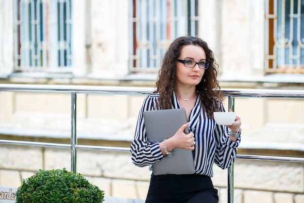 Young long-haired woman working with a laptop, sitting on an outdoor terrace in a cafe. business development concept, girl in the lunch break working over a cup of coffee