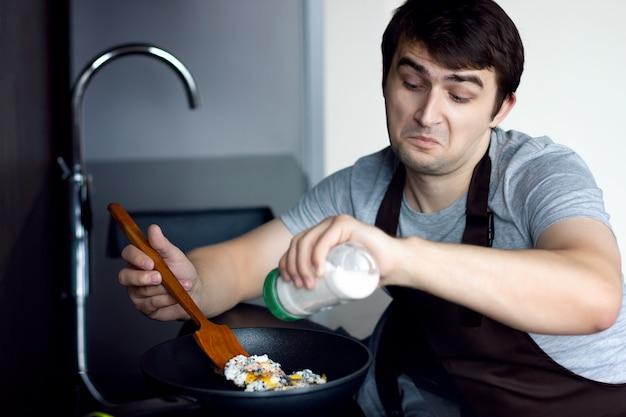 モダンなロフトキッチンで金属製のフライパンに塩を追加するスクランブル若い敗者男男性。朝食、ランチ、ディナーを作ろうとしています。女性の女性の概念なしのキッチンで一人で独身