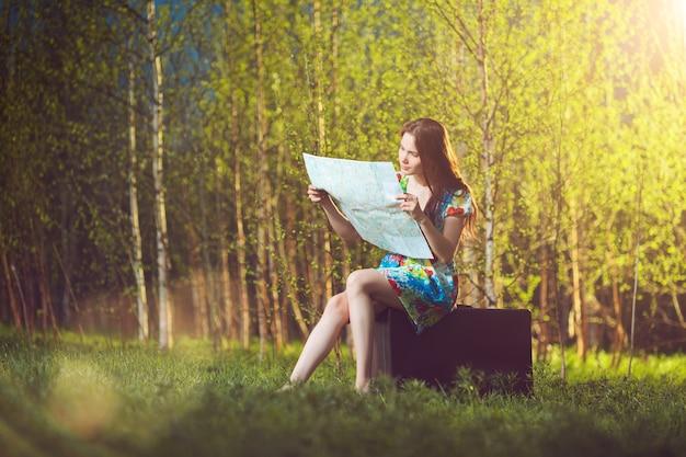スーツケースに座って森の中で地図を読んで若い失われた女性