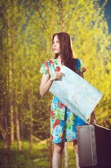 スーツケースと地図を持つ若い失われた女性