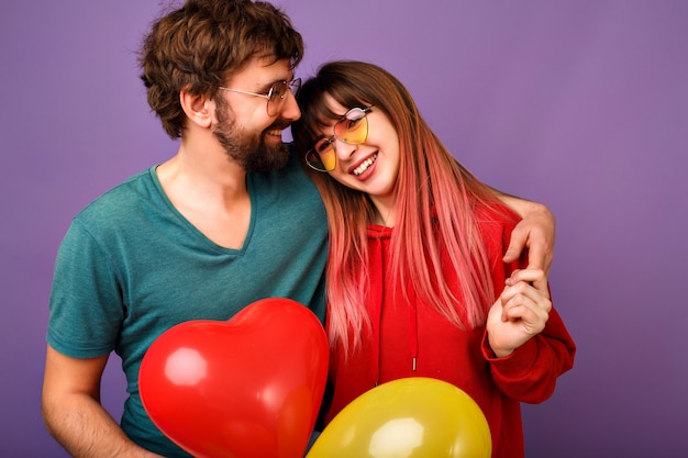 Young lovable hipster couple posing on violet wall, bright trendy casual clothes and glasses, hugs and smiling, friendship and relation goals, holding air balloons, ready for celebration.