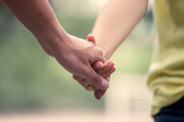 Young love couple holding hands and walk together in vintage color tone