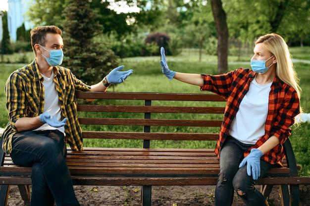 公園、検疫のベンチに座っているマスクと手袋の若い愛のカップル。流行、ヘルスケアと保護、パンデミックライフスタイルの間のロマンチックな会議