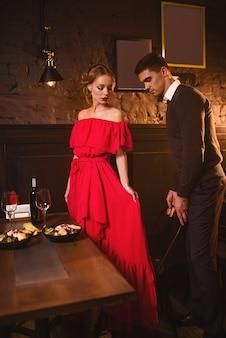 レストランでの若い愛のカップル、ロマンチックなデート。赤いドレスを着たエレガントな女性と彼女の男性の食事