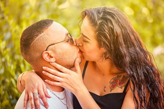 自然と日光に浸る日没で若い愛のカップルのキス