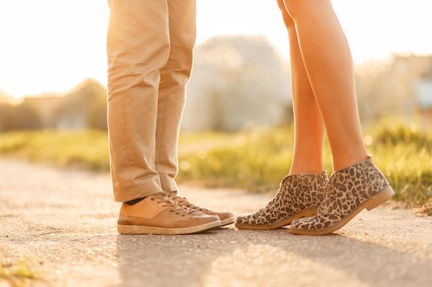Молодая влюбленная пара, целующаяся на закате. ноги с обувью крупным планом