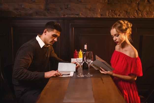 若い愛のカップルは、レストラン、ロマンチックなデートのメニューを見てください。赤いドレスを着たエレガントな女性とカフェに座っている彼女の男