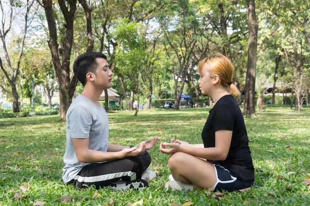 Young love couple making a meditation to calm their mind after exercising in park encircle