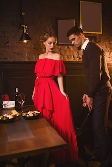 Young love couple in restaurant, romantic date. elegant woman in red dress and her man dining