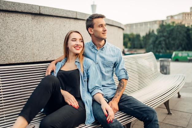 ヤングは、夏の都市公園のベンチに座っているカップルが大好きです。 10代の若者が一緒にポーズを笑顔、