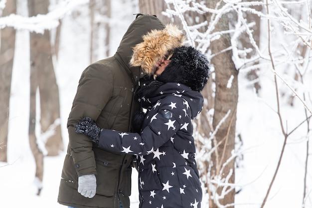 Молодые влюбленные пары, целующиеся в снежном парке зимнего сезона