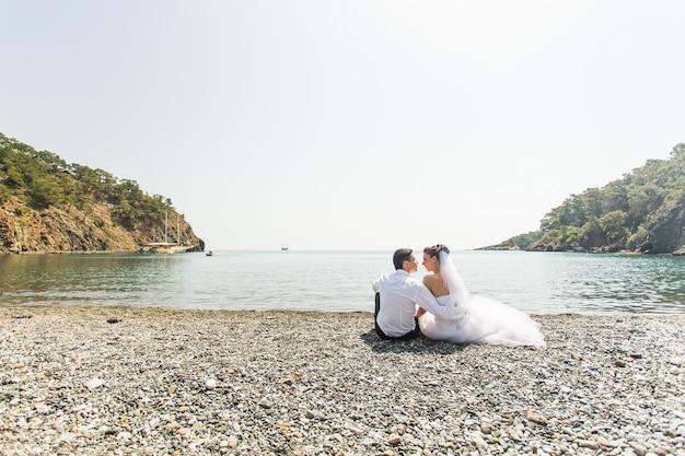 Молодые любят свадебные пары, сидели на пляже