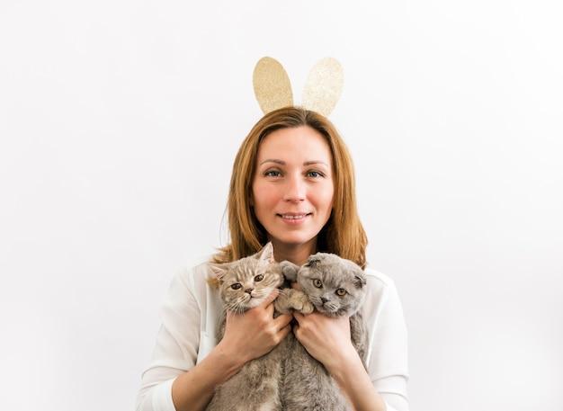 토끼 귀를 착용하고 고양이 두 마리와 즐거운 시간을 보내는 젊은 사랑스럽고 긍정적 인 여성.