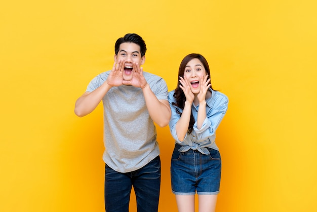Young lovely asian couple yelling with hands cup around mouths