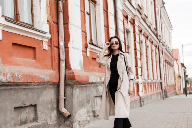 Молодая симпатичная красивая женщина-модель в модных солнцезащитных очках в модном бежевом плаще гуляет возле старинного здания в городе. симпатичная девушка гуляет по улице. весенняя модная одежда для женщин.