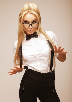 Young lovely blond woman with glasses posing in studio