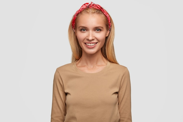 笑顔、長い髪、ヘッドバンドとベージュのカジュアルセーターを着て、前向きな感情を表現する若い素敵なブロンドの女性