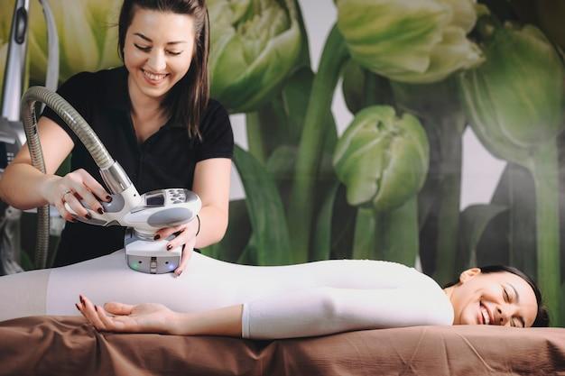 Молодая симпатичная кавказская женщина, опираясь на спа-кровать, после антицеллюлитных процедур с lpg косметологом в спа-салоне.