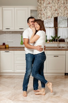 Young lovely couple embracing in kitchen