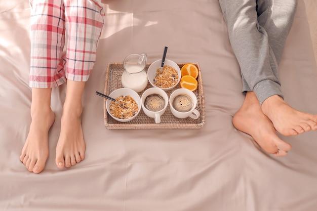 Молодая прекрасная пара завтракает на кровати