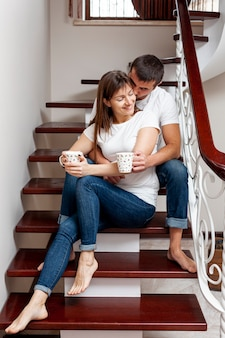 Young lovely couple holding  cups of coffee and sitting on stairs