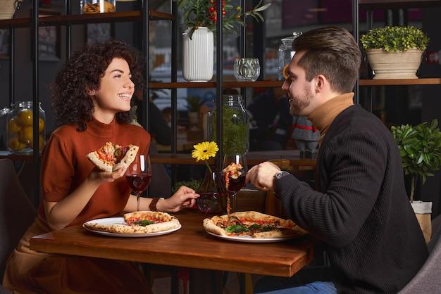 젊은 사랑스러운 부부는 피자 피자에서 피자를 먹고있다. 남자는 식당에서 그의 여자를 즐겁게합니다. 행복한 사람들이 함께 재미