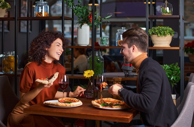 Young lovely couple is eating pizza it in pizzeria. guy is amuses his girl in a restaurant. happy people having fun together