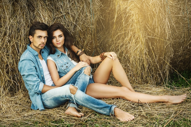 Young lovely couple is relaxing among the haystacks