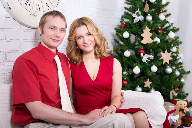Young lovely couple near decorated christmas tree
