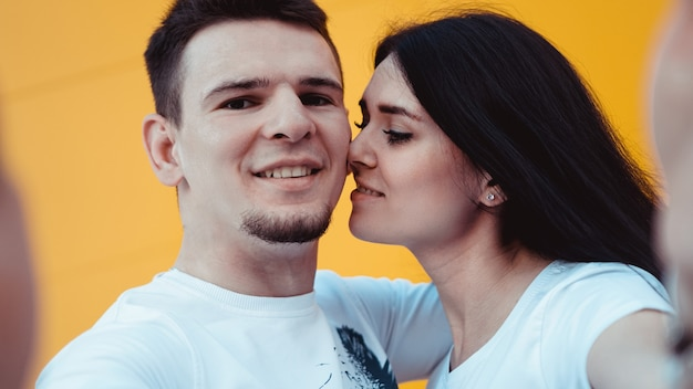 Young lovely couple posing together while making selfie on smartphone over yellow