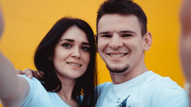 Young lovely couple posing together while making selfie over yellow