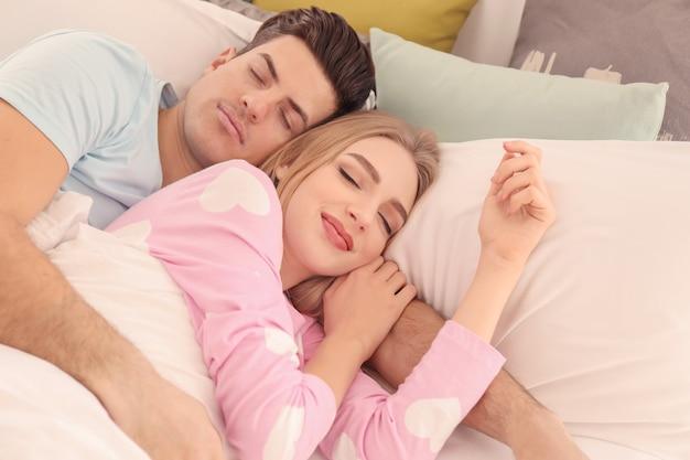 집에서 침대에서 자고 젊은 사랑스러운 부부