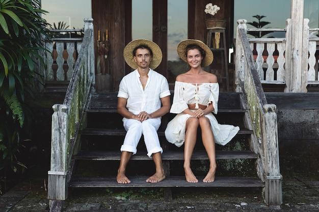 自然な服を着た若い素敵なカップルがベランダの階段に座っています