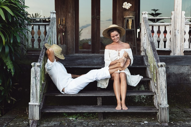 Young lovely couple wearing natural clothes are sitting on the stairs of the porch