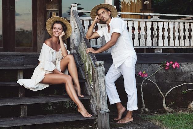 彼らの家のポーチに座っている自然な服を着ている若い素敵なカップル
